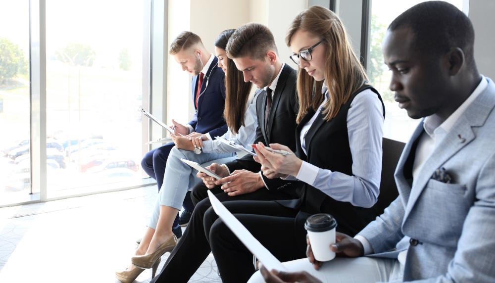 Groupe de personne en tenue de travail, qui attendent pour un entreten d'embauche